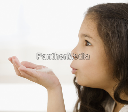 hispanic girl blowing on feather in