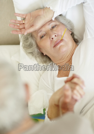senior woman with a thermometer in