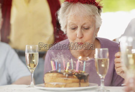 senior woman blowing out the candles