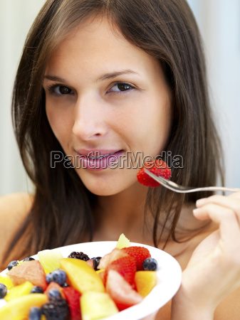 woman eating fresh fruit