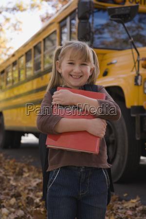 girl hugging school book in front