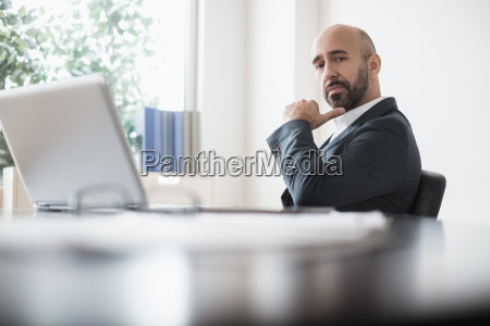 serious businessman sitting at desk in