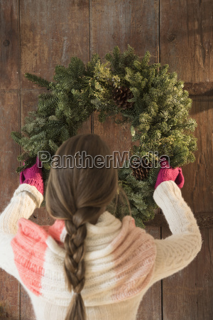 young woman hanging christmas wreath on