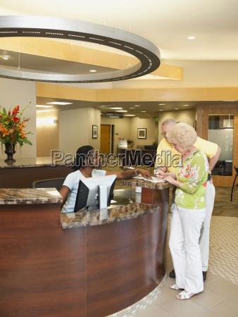 senior people at reception desk in