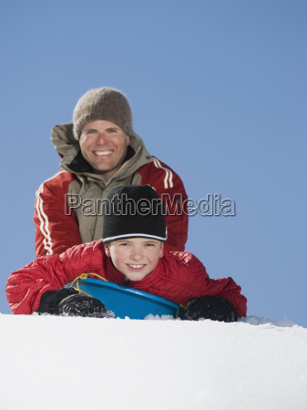 father and son on sled in