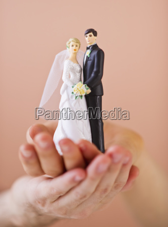 couple holding small wedding figurine