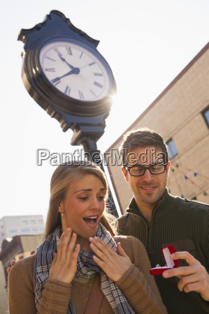 man proposing to woman on street