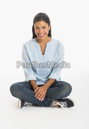 studio shot woman sitting cross legged