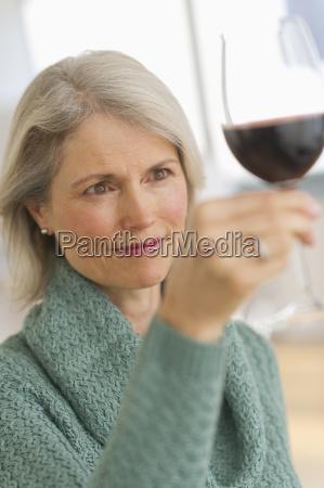 senior female connoisseur tasting red wine