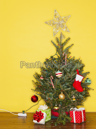 small christmas tree against yellow wall