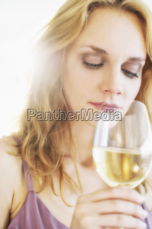 portrait of young woman smelling wine