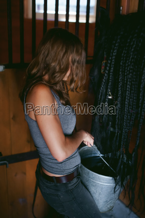 female horseman holding a bucket of