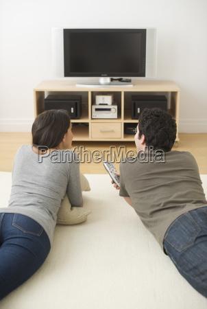 couple lying on floor watching tv