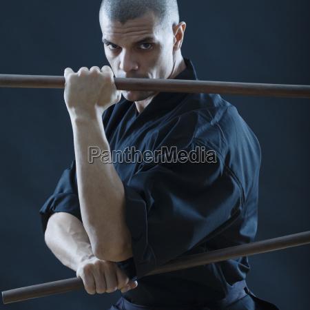 hispanic, male, holding, sticks, in, fighting - 24065614