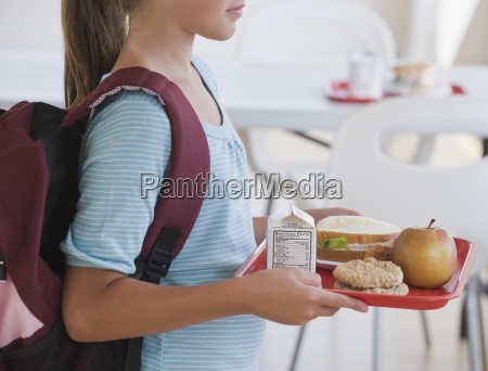 girl carrying lunch tray at school