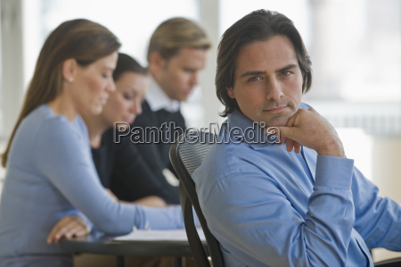 portrait of businessman with business people