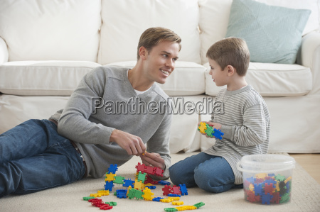 father playing with son in livingroom