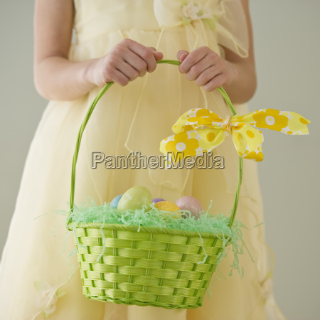young girl holding a basket of