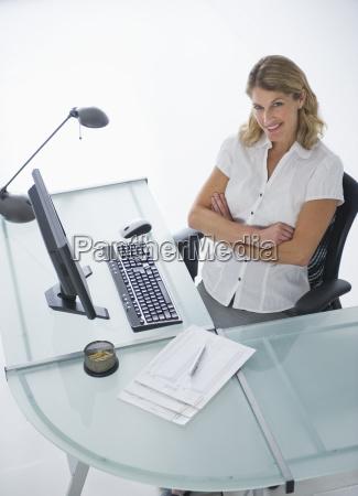 confident businesswoman sitting at modern desk