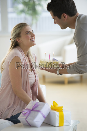 man giving birthday cake to woman