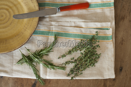 rosemary and thyme with kitchen knife