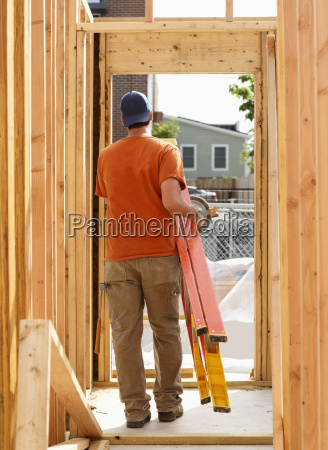 caucasian man carrying ladder at construction