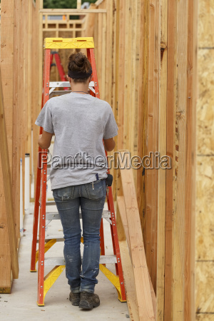 caucasian woman pushing ladder at construction