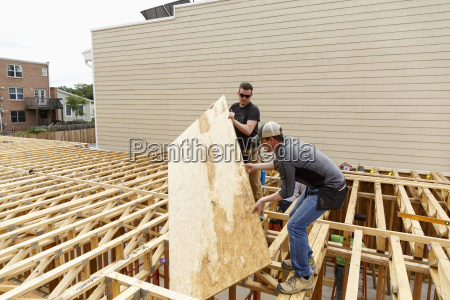 caucasian men carrying plywood at construction
