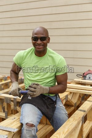 black man posing with hammer at