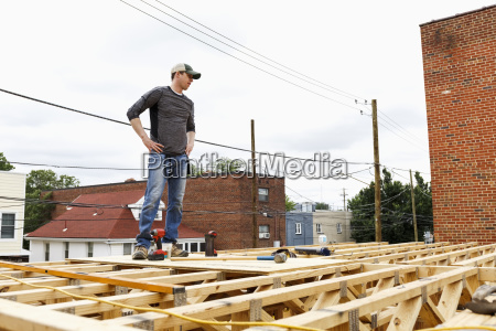 caucasian man standing on the roof