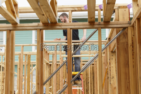 caucasian man standing on ladder at