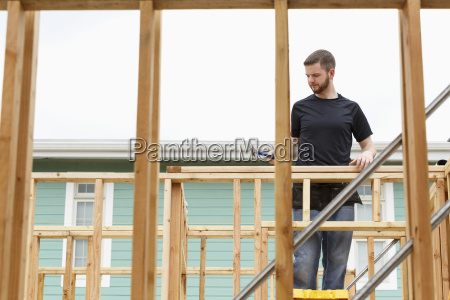 caucasian man on ladder using hammer