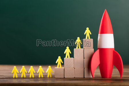 rocket besides yellow human figures on