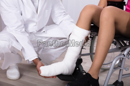 doctor holding disabled womans leg