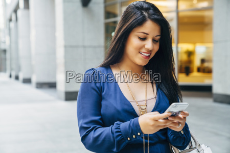 close up of hispanic woman texting