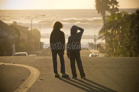 boys standing in street admiring ocean