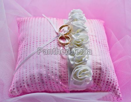wedding rings on pink cushion