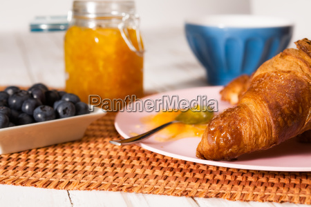 closeup of croissant and blueberries over