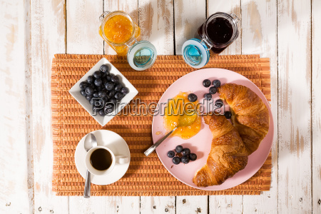 breakfast with croissant blueberries coffee and