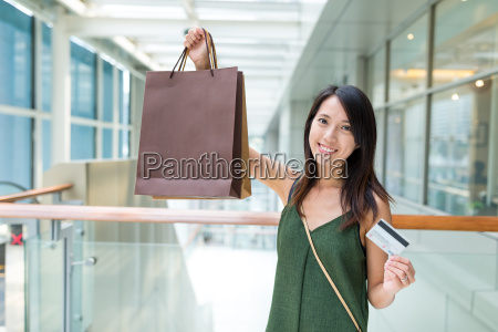 woman holding shopping bag and credit