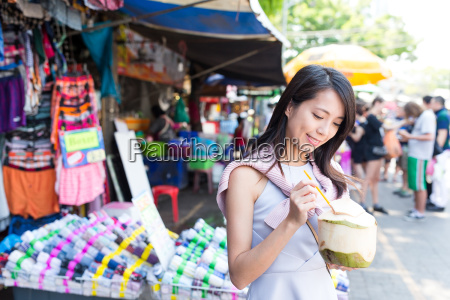young woman having coconut juicy in