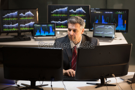 stock market broker looking at multiple