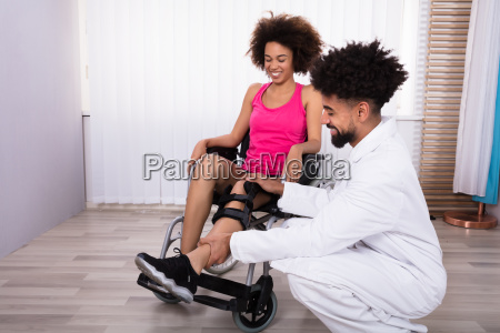 physiotherapist fixing knee braces on womans