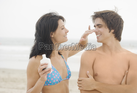 woman putting sunscreen on mans nose