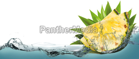 pieces of pineapple in water splashes