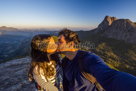 couple kissing while taking selfie in