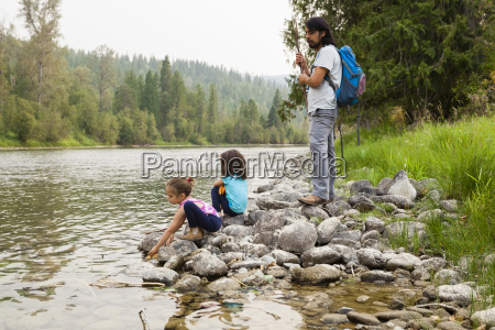 father and daughters hiking resting at