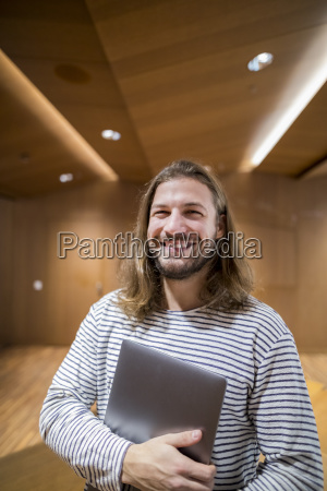 portrait of laughing man with laptop
