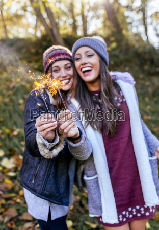 two happy women holding sparklers in