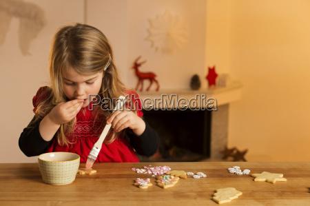 little girl garnishing christmas cookies with